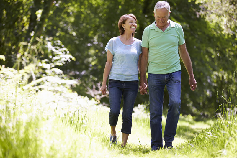 a mature couple holding hands and walking in a meadow