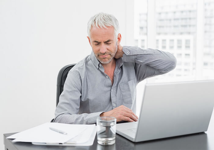 a mature man sitting at a desk with upper back pain