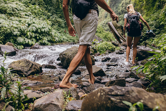 a young couple walking barefoot in a stream