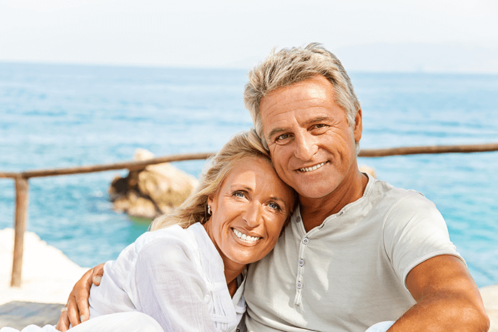 mature smiling couple beside the sea