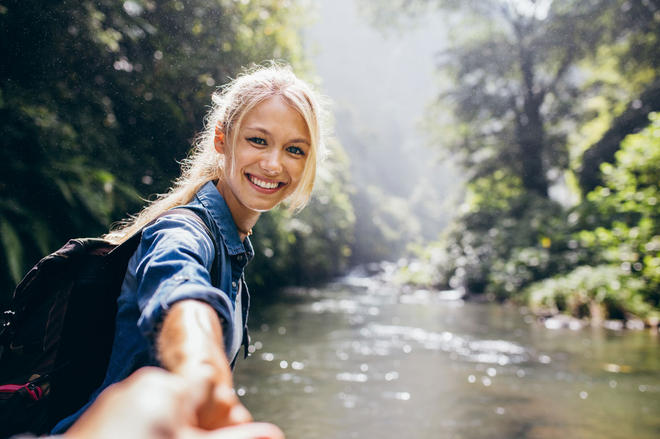smiling young woman standing in a stream