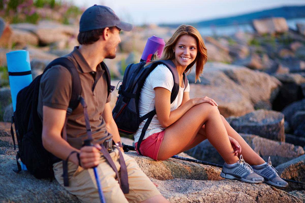 a smiling young man and woman sitting on a rocky beach